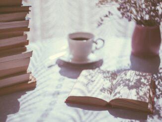 Książki, filiżanka kawy i bukiet kwiatów na stole.